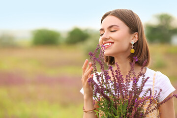 Fototapeta Beautiful young woman with summer flowers in blooming field obraz