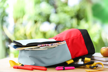 Fototapeta School backpack with stationery on table outdoors obraz