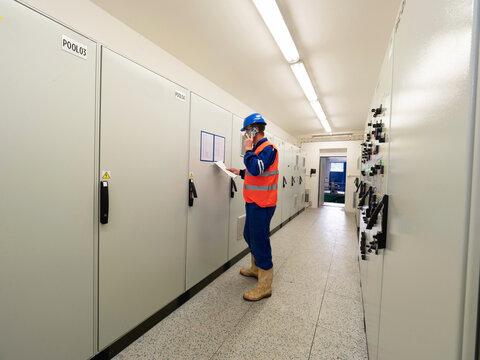 Industrial engineer using phone in machin control room