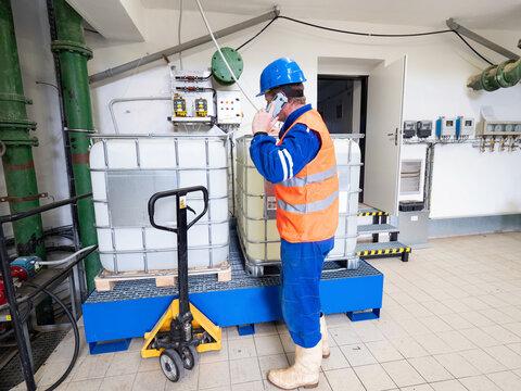 Calling worker. Industrial engineer using phone in industry room.