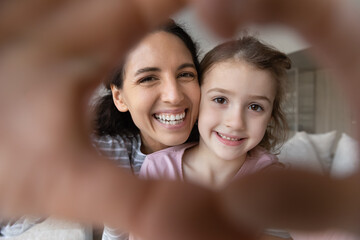 Close up self-portrait picture of happy young Hispanic mom and small teen biracial daughter have...