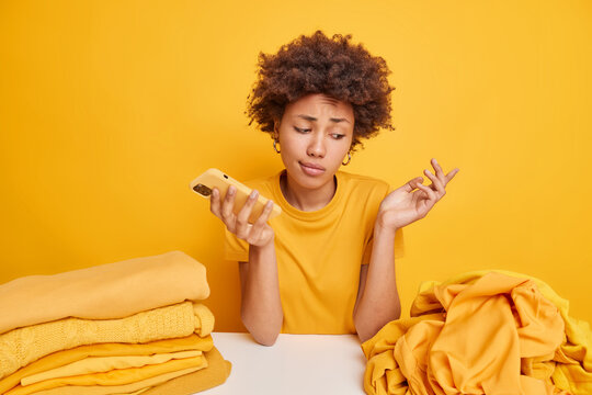 Clueless hesitant Afro American woman shrugs shoulders doesnt know what to do with unused clothes looks at pile of unfolded laundry sits at table holds smartphone isolated on yellow background