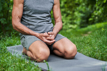 Man sitting at the knees at the yoga mat while preparing to the training
