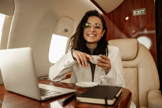 Happy and smiling woman moderator flies on a private business plane, happy with her results, drinks tea and works on board