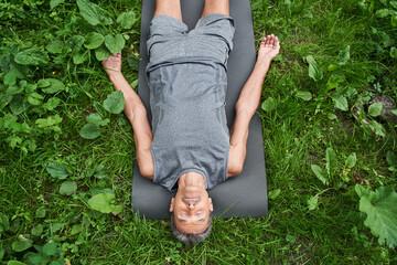 Fototapeta Man laying on sport mat, relaxing in savasana pose after exercising at the fresh air obraz