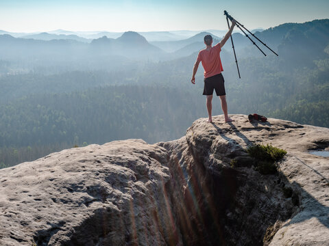 The photographer holds a tripod with a camera high in the air  and enjoy day