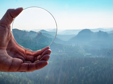 Crystal glass ball in a man's hand. The morning misty hilly landscape