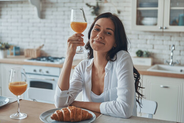 Fototapeta Beautiful young woman holding glass with juice smiling while spending time in the domestic kitchen obraz