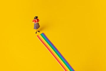 Fototapeta Adult woman figure stand on rainbow LGBT strip on yellow background obraz