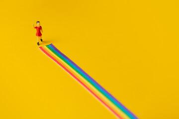 Fototapeta little girl figure on the LGBT rainbow path obraz