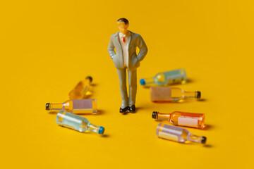Fototapeta miniature figure of a man with alcohol bottles around him obraz