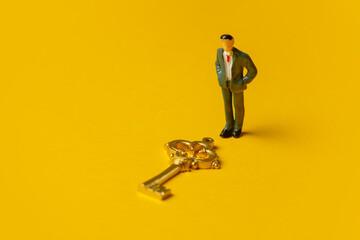 Fototapeta miniature figure of a man neat golden key on yellow background obraz