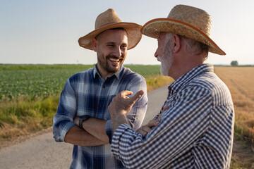 Fototapeta Two farmers standing on road next to field talking laughing. obraz