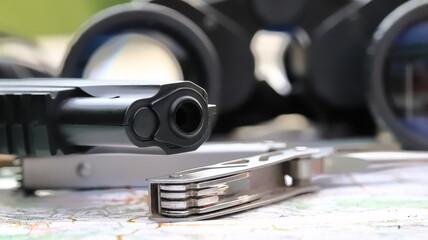 Fototapeta lufa pistoletu na tle lornetki, barrel of a gun against the background of binoculars obraz
