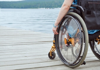 Fototapeta Woman in a wheelchair looking at the sea, part of the image, with copy space obraz
