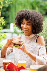 Vivacious happy young black woman eating a hamburger