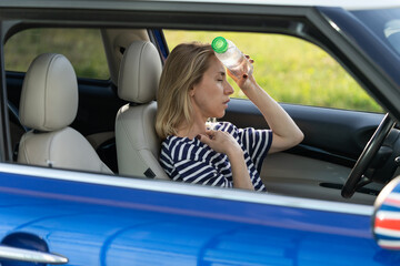 Obraz Exhausted woman driver feeling headache, sitting inside her car, applies bottle of water to forehead, hot weather. Tired female stop after driving car in traffic jam. Blood pressure, heat concept.  - fototapety do salonu