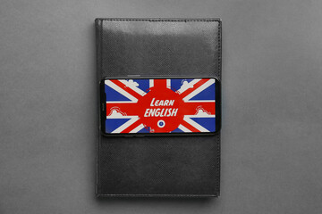 Notebook and phone with UK flag on screen against grey background. Concept of learning English