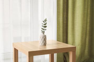 Fototapeta Table with vase near light curtains in room obraz