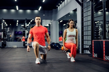 Fototapeta A cute sports couple exercising steps forward for legs and buttocks on a black floor in an indoor gym with a mirror. Fitness and sports lifestyle obraz