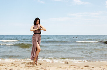 young brunette woman stands on the sand by the sea