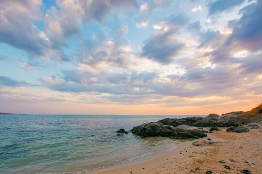 summer vacation landscape by the sea at sunrise. calm water washes sandy beach. dramatic clouds above horizon in morning light on the sky
