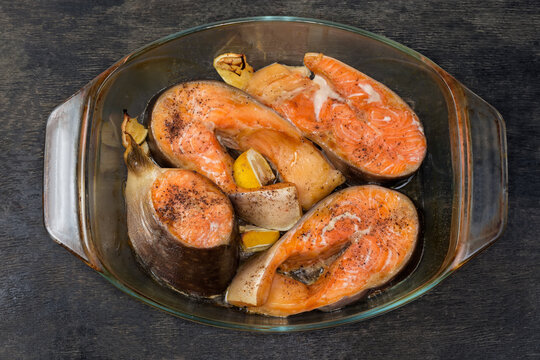 Baked trout in baking dish on dark surface, top view
