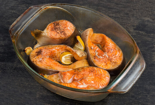 Baked trout pieces in glass baking dish on dark surface