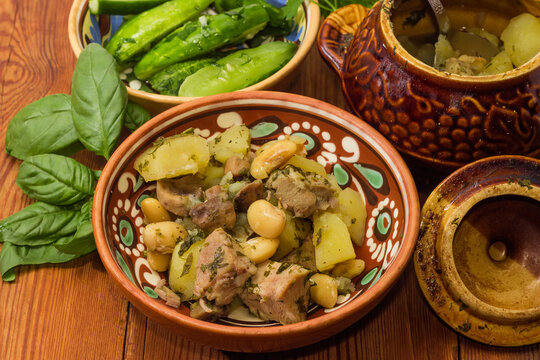 Meat stewed with vegetables in clay pot on rustic table