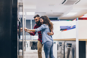 Fototapeta Young couple, satisfied customers choosing fridges in appliances store. obraz