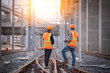Obraz Engineer under inspection and checking construction process railway switch and checking work on railroad station .Engineer wearing safety uniform and safety helmet in work - fototapety do salonu