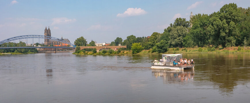 Panoramic view over old cathedral at historical downtown in Magdeburg with a touristic party boat with many girls coming by at Elbe river, Germany, at blue summer sky with clouds.