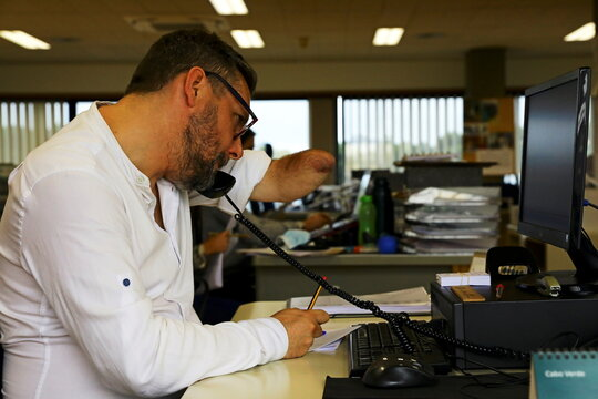 Rui Brito, a worker with a disability, answers a work call in Porto