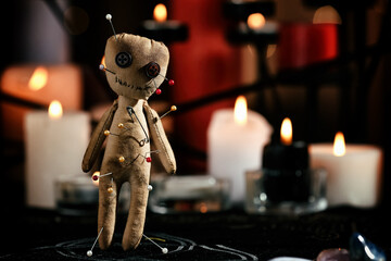 Obraz Voodoo doll pierced with pins on table in dark room, space for text. Curse ceremony - fototapety do salonu