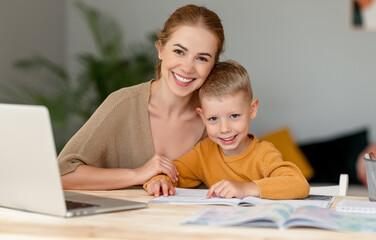 Fototapeta Happy mother supporting son during online studies obraz