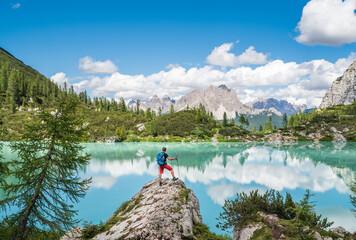 Backpacker with backpack enjoying the turquoise Lago di Sorapiss 1,925m altitude (mountain lake)...
