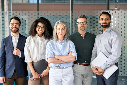 Happy diverse business people team standing together in office, group portrait. Smiling multiethnic international young professional employees company staff with older executive leader look at camera.