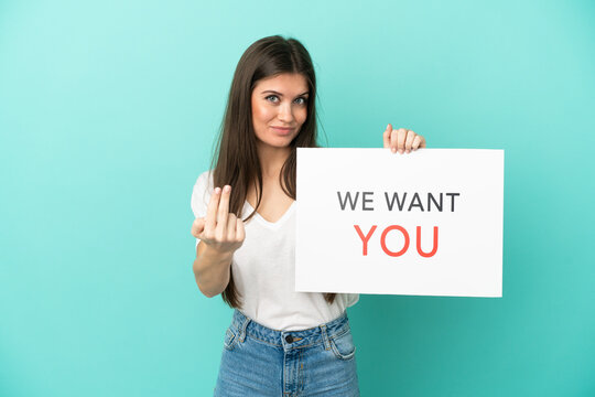 Young caucasian woman isolated on blue background holding We Want You board and doing coming gesture