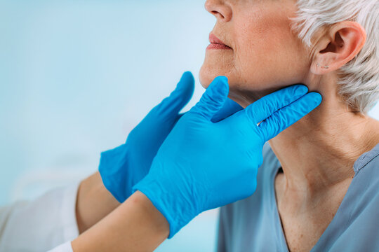 Thyroid Gland Control. Endocrinology Doctor Examining Senior Woman at Clinic.