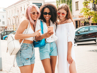 Fototapeta Three young beautiful smiling hipster female in trendy summer clothes.Sexy carefree multiracial women posing in the street.Positive models in sunglasses. Looking at smartphone screen.Using phone apps obraz