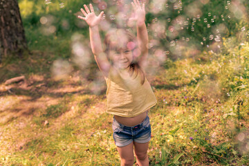 Obraz cute kid girl catches a lot of soap bubbles on a summer day, child in blur - fototapety do salonu