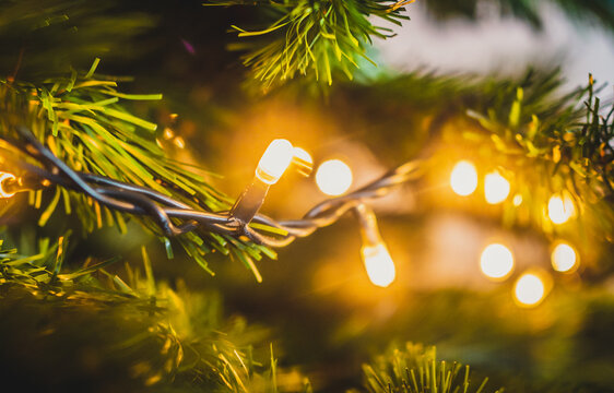 Closeup of glowing yellow Christmas lights on a tree with a blurred background - Christmas wallpaper
