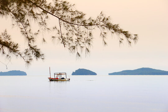 Beautiful sea landscape, lonely traditional khmer boat and distant islands, morning mist at the background of sky and blured tree branch, Sihanouk ville, Gulf of Thailand, Cambodia, South East Asia