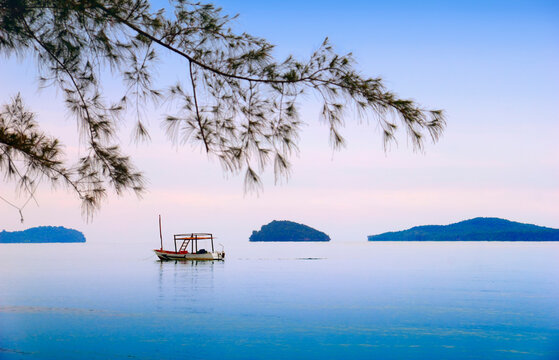 Beautiful sea scape with lonely traditional khmer boat, distant islands in morning mist, blue sky, blurred tree branch in Otres beach, Sihanouk ville, Gulf of Thailand, Cambodia, South East Asia