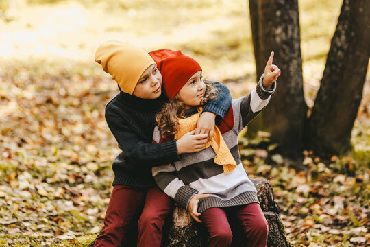 Happy playful children friends in warm clothes a hat in bright hats and scarves are walking having fun sitting on a stump and a pumpkin catching leaves in the autumn forest in nature, selective focus