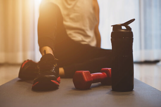 Young athlete wearing gray t-shirt and black sport shoe is sitting down after weight training workout at home with personal trainer with water bottle and a dumbbell placed on yoga mat.