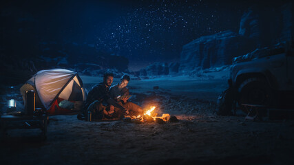 Fototapeta Happy Couple Nature Camping in the Canyon at Night, Use Digital Tablet Computer, Sitting by Campfire. Two Traveling people Have Fun, Smile, Post on Social Media, Watch Funny Videos on Internet obraz