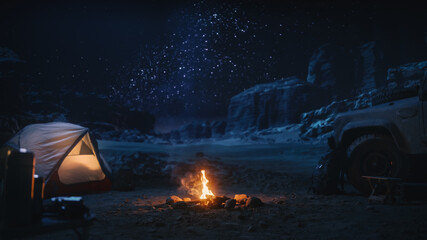 People Camping at Night in the Canyon, Preparing to Sleep in the Tent. Campfire barely Burning,...