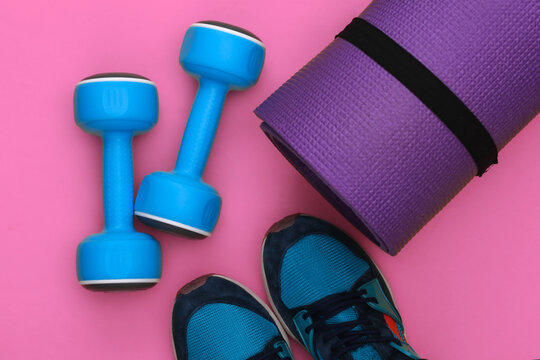 Sport shoes, fitness mat and dumbbells on pink background. Healthy lifestyle, fitness training. Top view. Flat lay