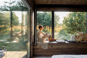 Young woman resting at beautiful country house or hotel, sitting on the window sill enjoying...